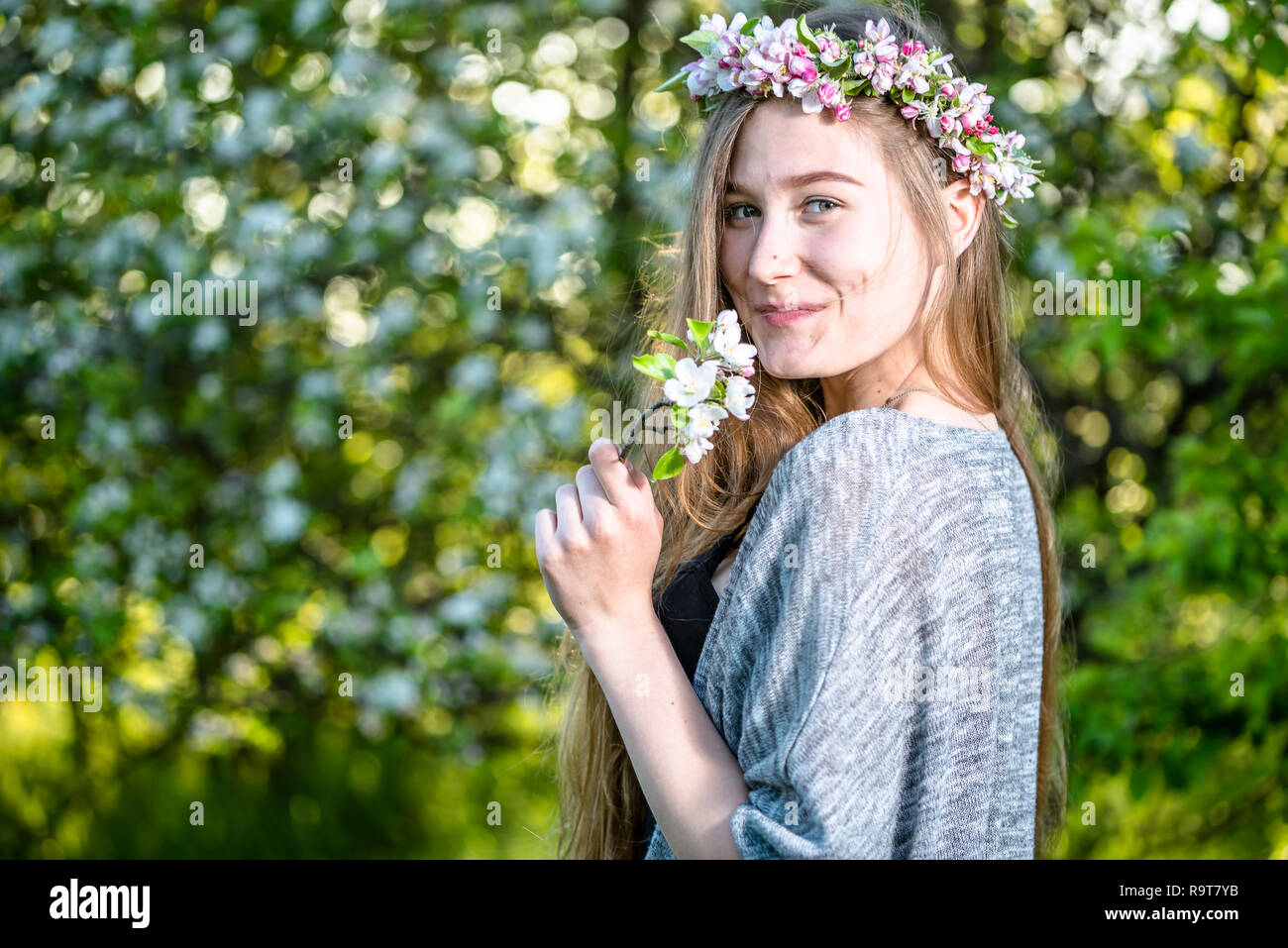 Happy young woman with spring blossom in the garden. Girl smelling flower  of apple tree e6b3d666c