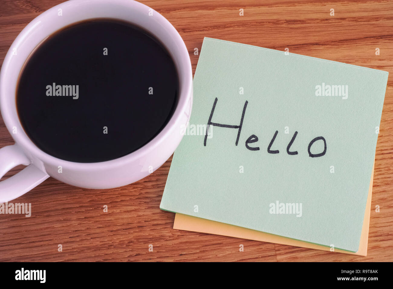 Hello. Post it note with writing Hello and cup of coffee. Close up. - Stock Image