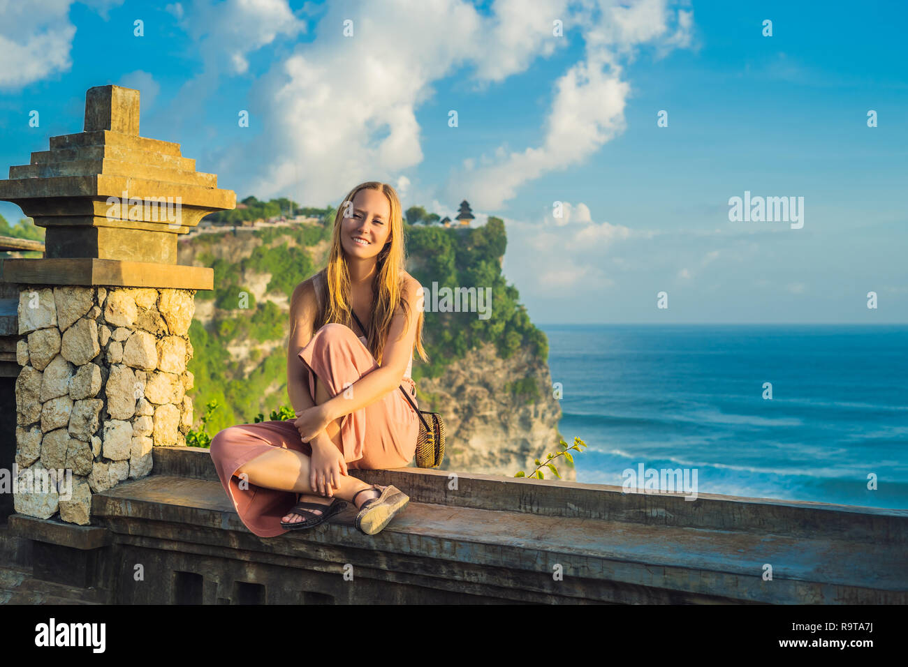 Young woman traveler in Pura Luhur Uluwatu temple, Bali, Indonesia. Amazing landscape - cliff with blue sky and sea Stock Photo