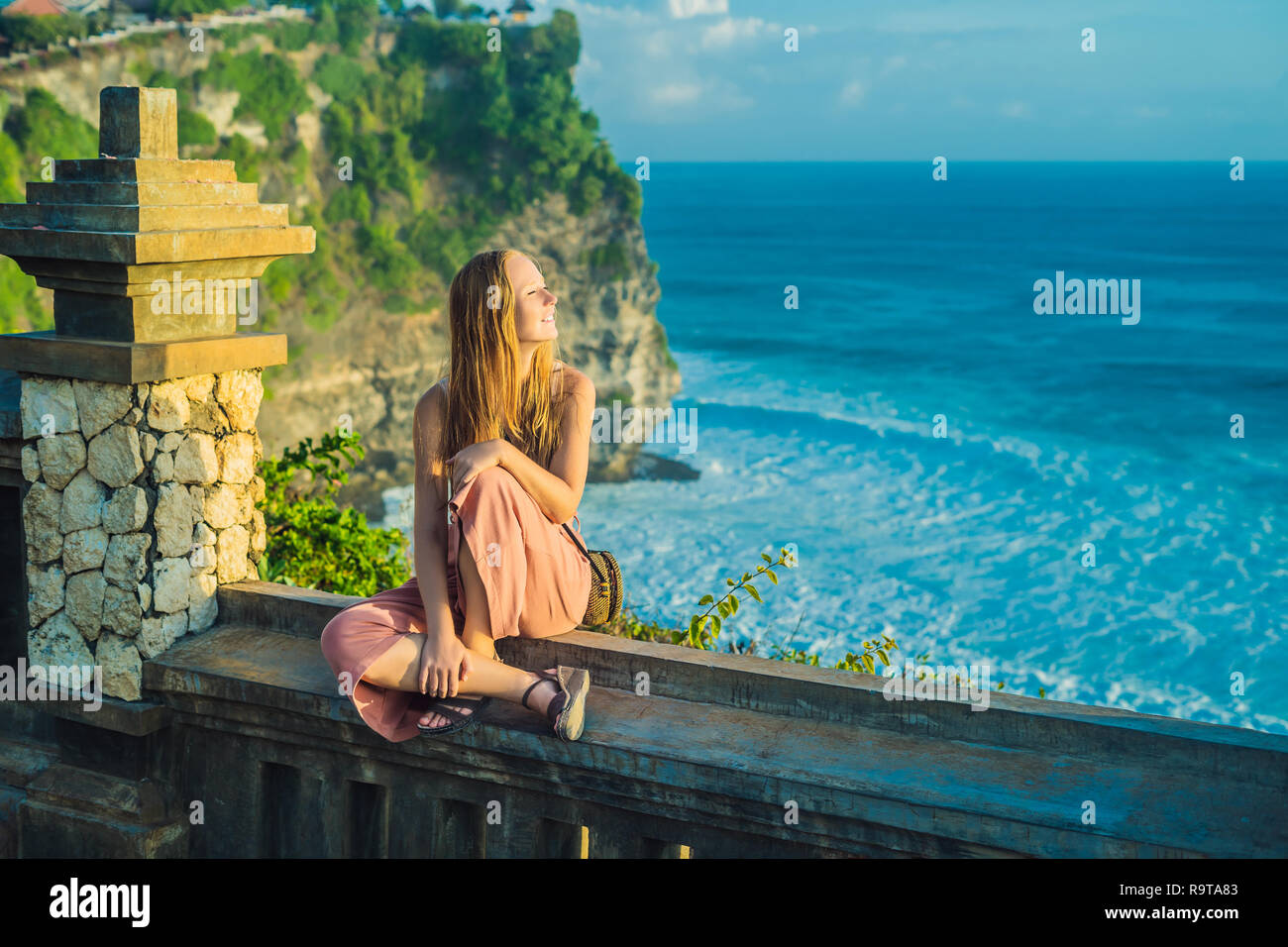 Young woman traveler in Pura Luhur Uluwatu temple, Bali, Indonesia. Amazing landscape - cliff with blue sky and sea - Stock Image