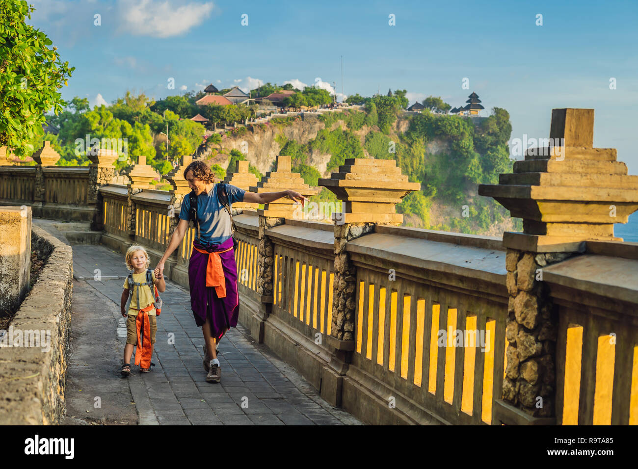 Dad and son travelers in Pura Luhur Uluwatu temple, Bali, Indonesia. Amazing landscape - cliff with blue sky and sea. Traveling with kids concept - Stock Image