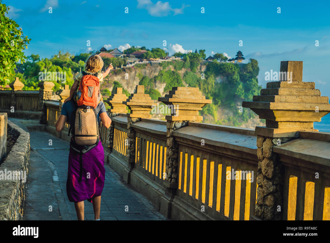 Dad and son travelers in Pura Luhur Uluwatu temple, Bali, Indonesia. Amazing landscape - cliff with blue sky and sea. Traveling with kids concept Stock Photo
