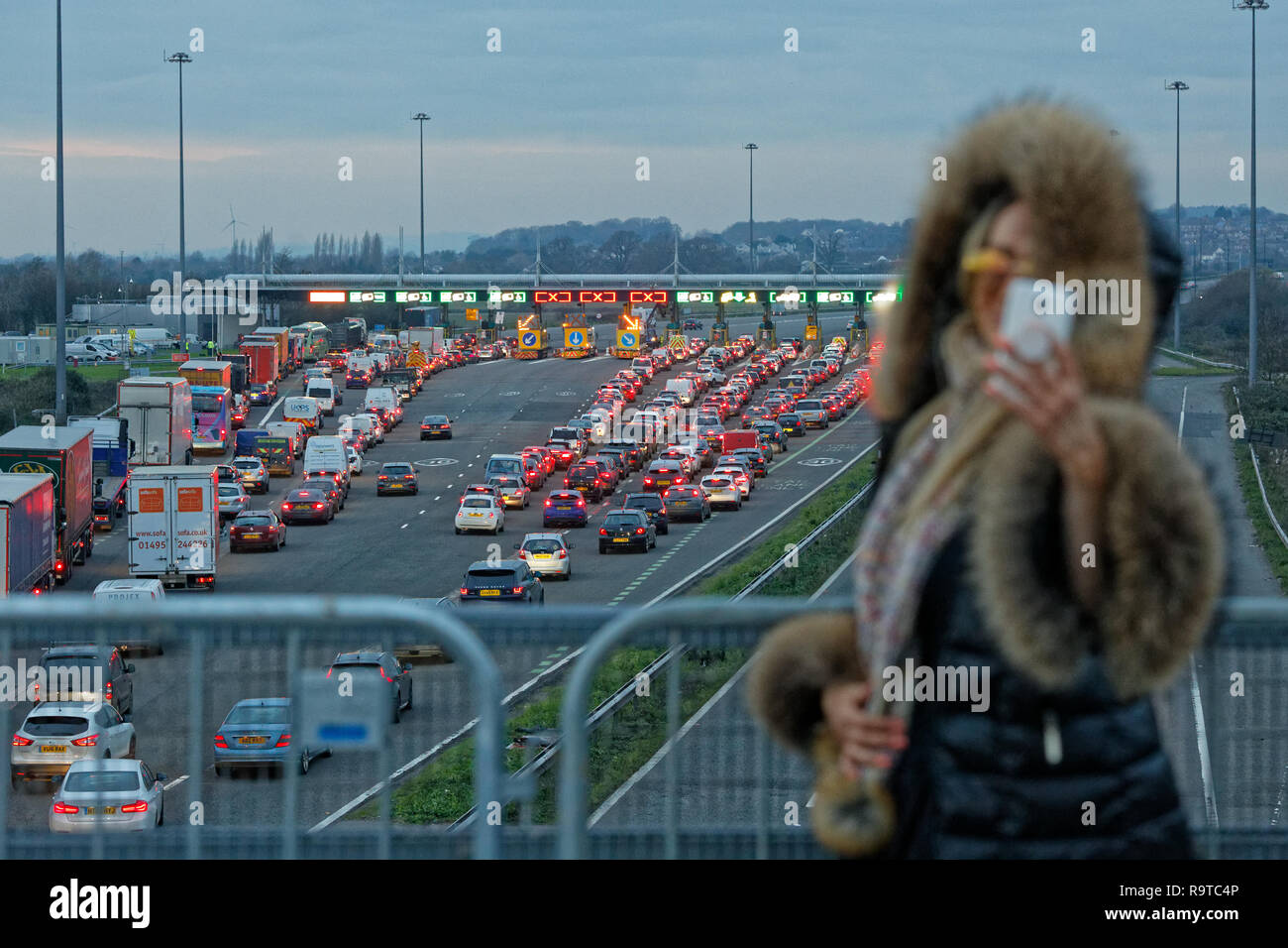 Pictured: A woman stands on a bridge to take a selfie on her mobile phone while long queues of cars form by the Severn Bridge tolls on the westbound c - Stock Image