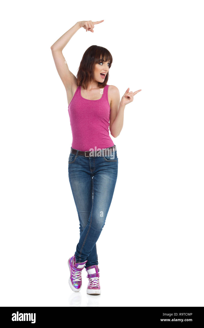 Young woman in magenta tank top, jeans and sneakers is standing, pointing, looking away and talking. Full length studio shot isolated on white. - Stock Image