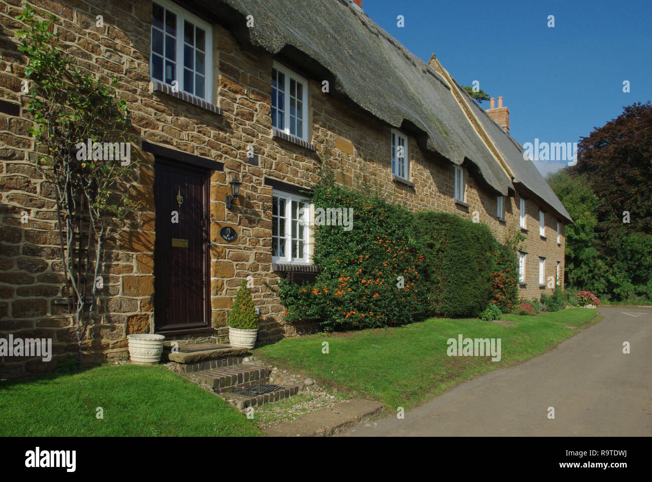 Row of picturesque stone built thatched cottages in the village of Ashby St Ledgers, Northamptonshire, UK Stock Photo