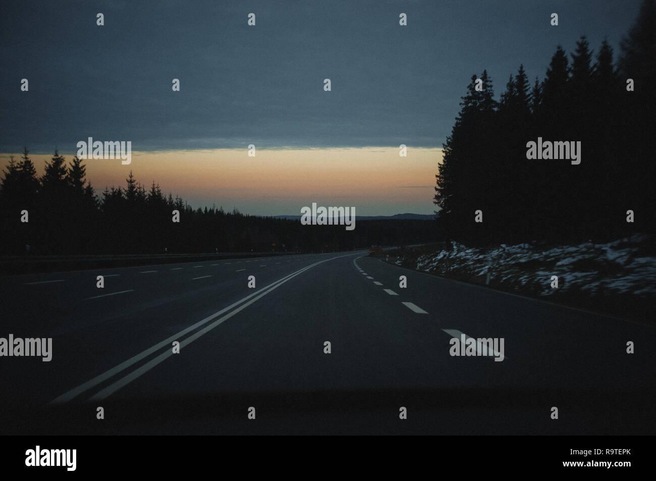 open road through the woods in beginning night in harz, niedersachen, lower saxony, germany - Stock Image