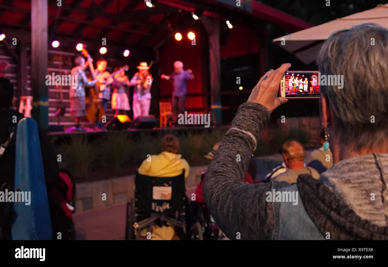 Maitland, FL USA. Feb 2016. Elderly woman snaps a smartphone picture of a Canadian band raising money for maple farm support. - Stock Image