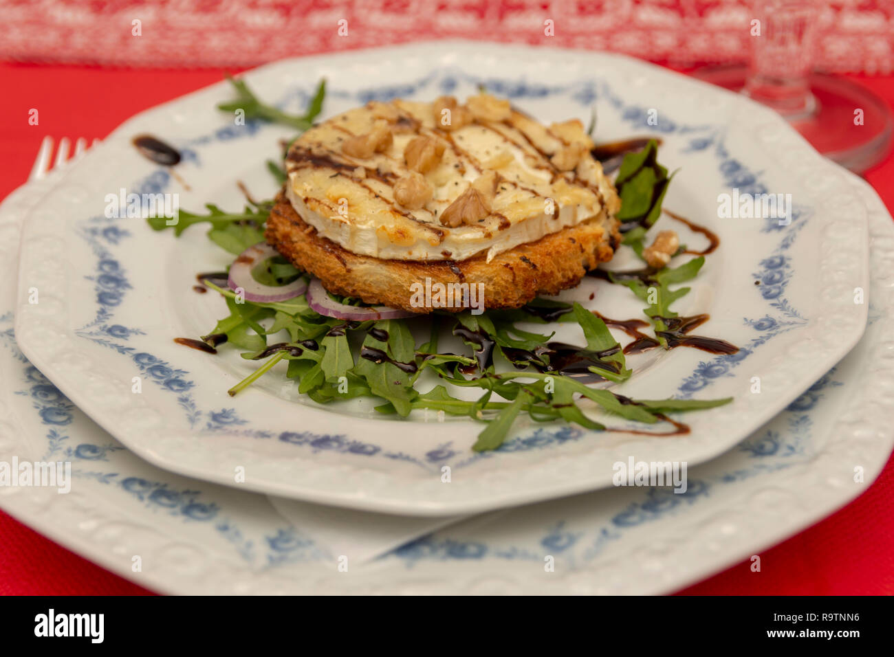 Plate with a roasted bred with a slice of chevre cheese and on top nuts and honey. - Stock Image