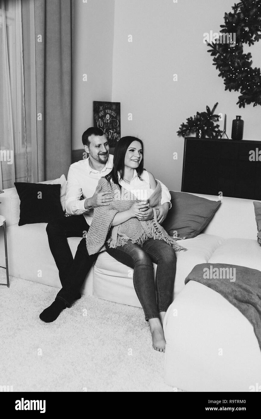 Happy husband and wife sitting on white sofa with plaids and pillows. Beautiful woman and man holding cups of tea in hands. Living room decorated with - Stock Image