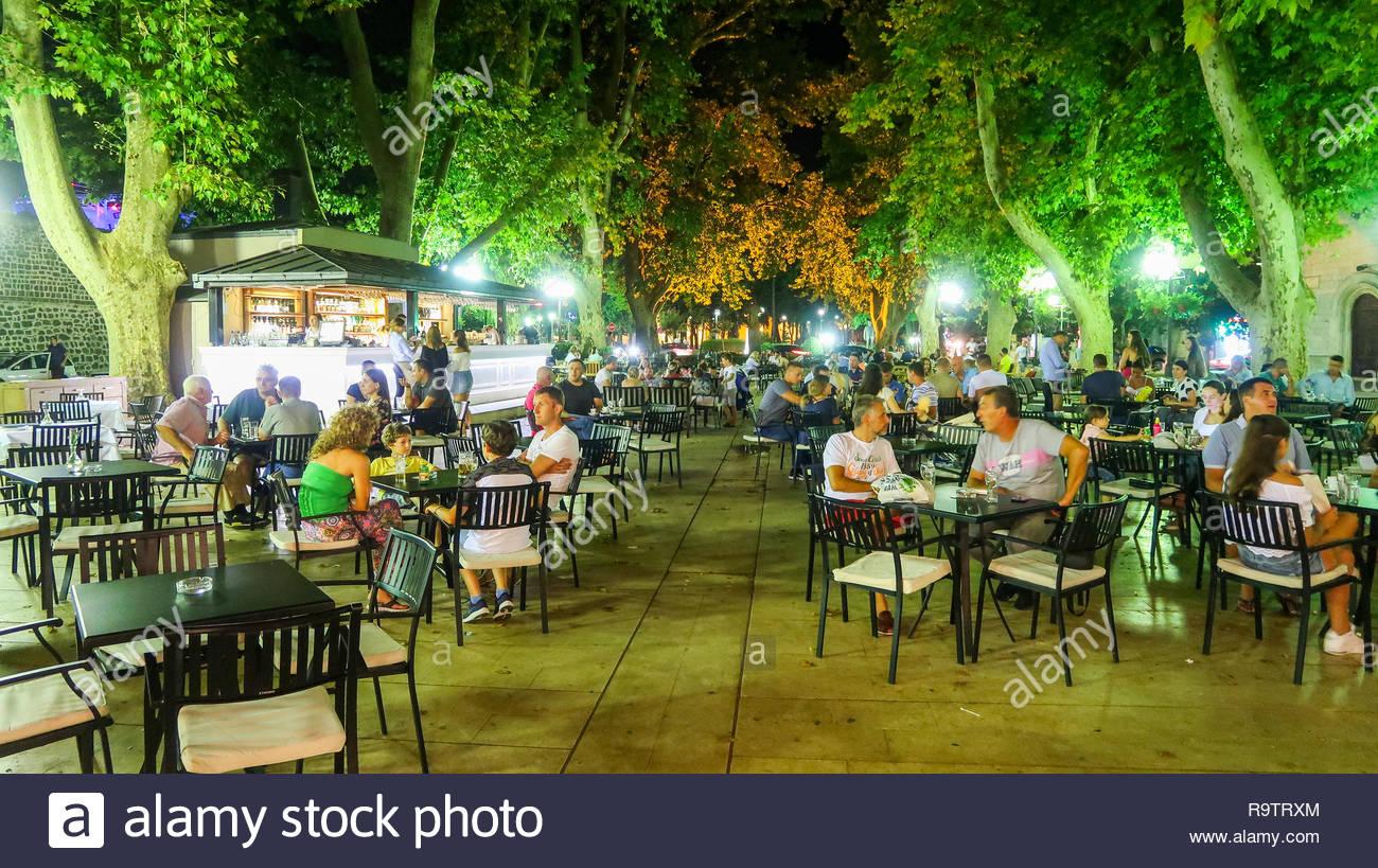 People Sitting in an Open Air Restaurant or Coffee Shop in Trebinje, Bosnia and Herzegovina (03.08.2018) - Stock Image