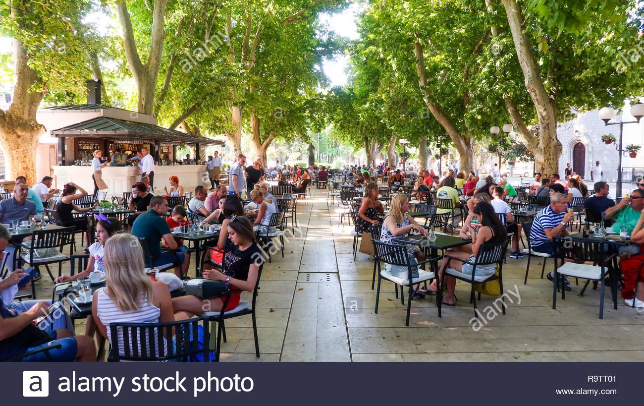 People Sitting in an Open Air Restaurant or Coffee Shop in Trebinje, Bosnia and Herzegovina (04.08.2018) - Stock Image