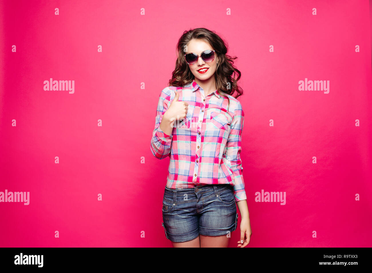 Studio portrait of funny girl in sunglasses showing peace sign with bare teeth over bright magenta background. Isolate. - Stock Image