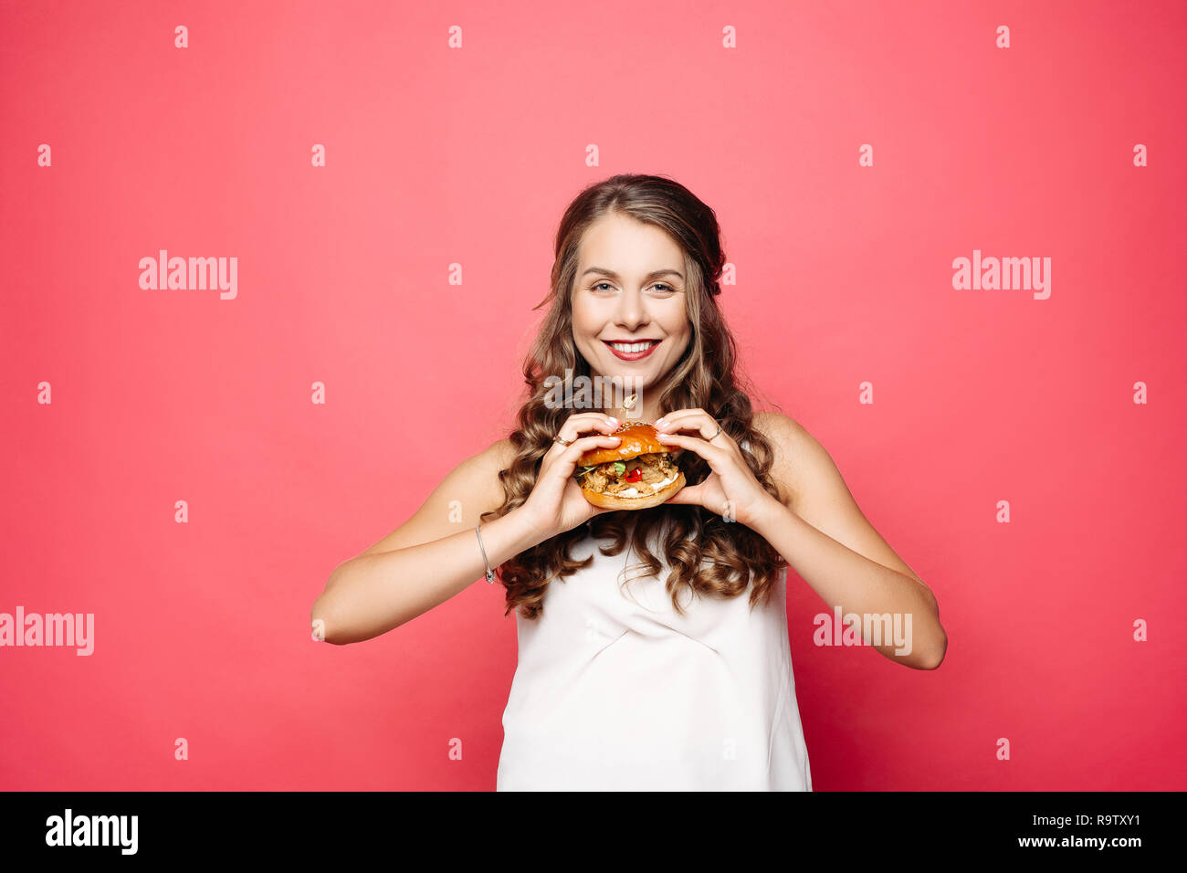 Close up of hungry girl with opened mouth, holding and eating big hamburger. Pretty woman with curly hairstyle and red lips eating tasty cheeseburger  Stock Photo