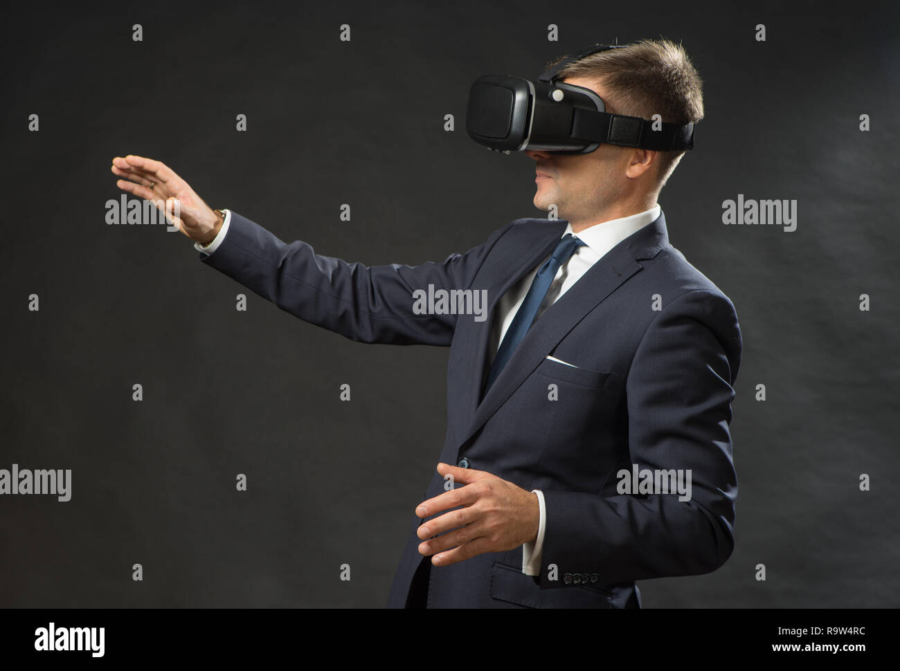 3a62261f6565 360. Virtual game. Man in black suit uses a virtual reality glasses ...