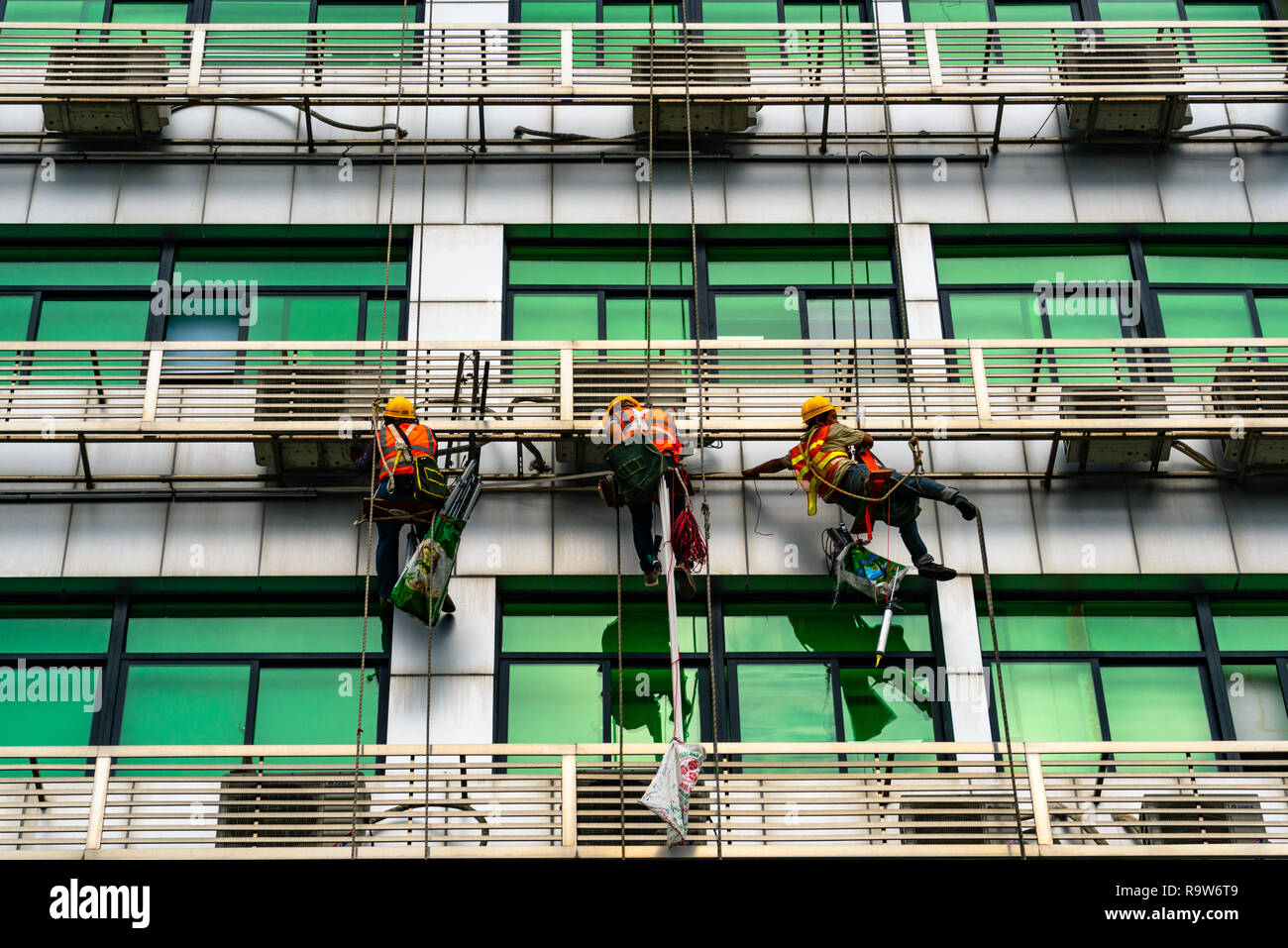 Occupation: repairmen suspended by cables at building exterior in Shenzhen, China Stock Photo