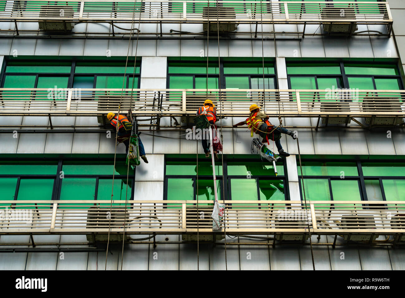 Occupation: repairmen suspended by ropes at building exterior in Shenzhen, China Stock Photo