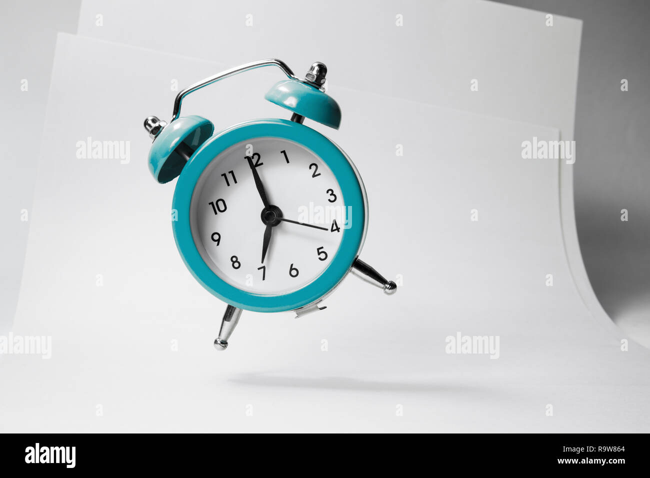 The blue alarm clock bounces against the background of business papers. - Stock Image
