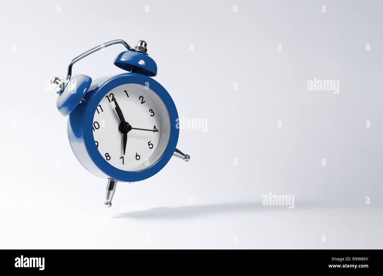 The dark blue alarm clock bounces against the background. - Stock Image
