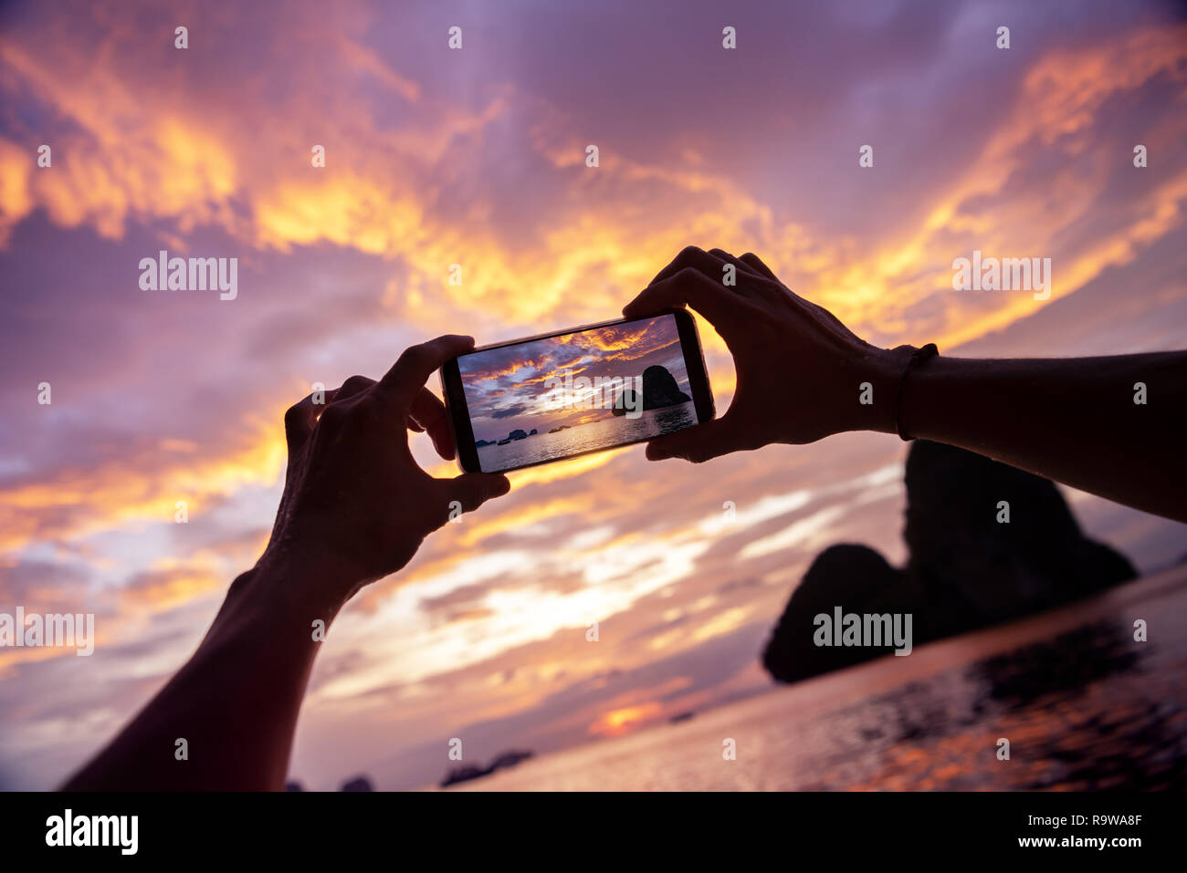 Closeup photo of hands taking a photo from mobile phone. Krabi province, Railay beach on background Stock Photo