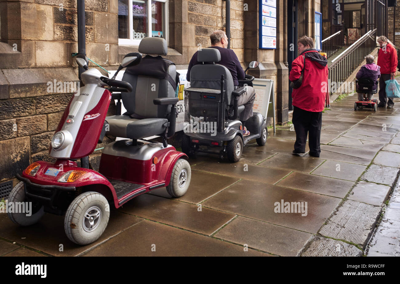 Three mobility scooters outside on pavement in the centre of Lancaster, northern Britain - Stock Image