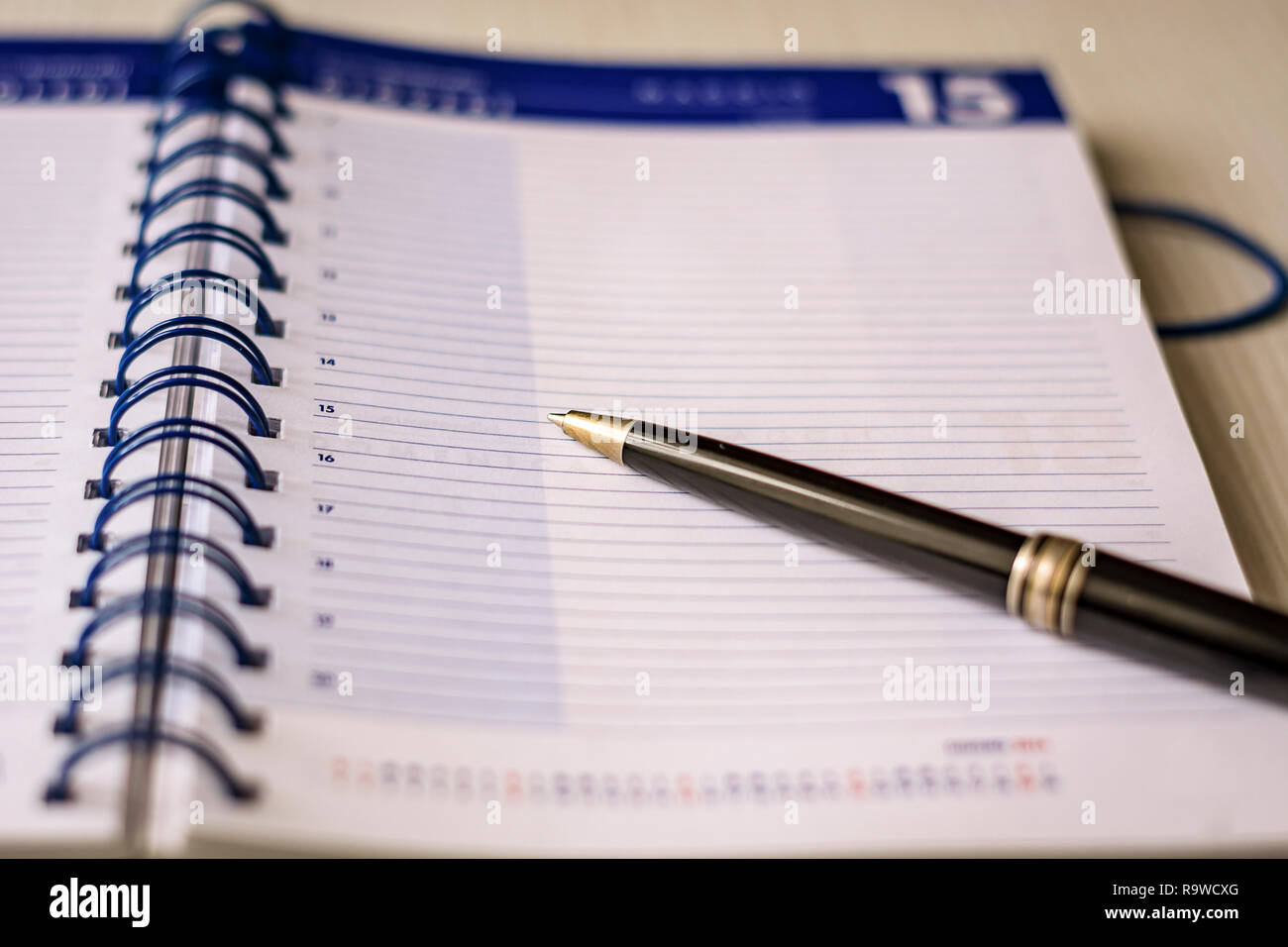 a black pen on an open spiral notebook. Business and scheduling concept - Stock Image