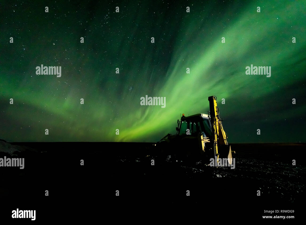 A frontloader is sidelit while the northern lights is visible overhead. - Stock Image