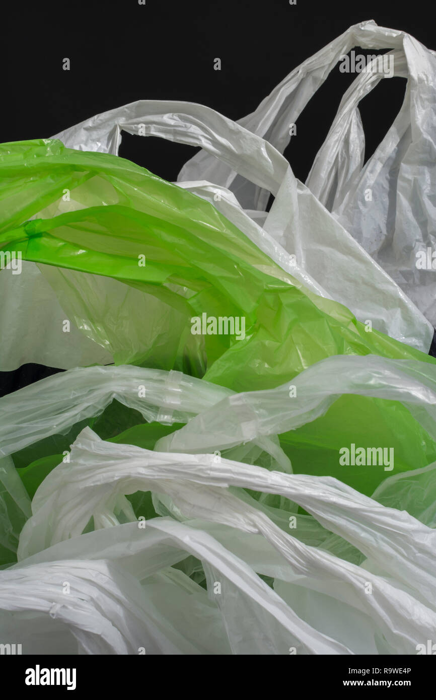 Multiple plastic shopping bags / carrier bags. Metaphor plastic bag tax, bag charge, war on plastic, plastic pollution UK. RM as identifiable colours. Stock Photo