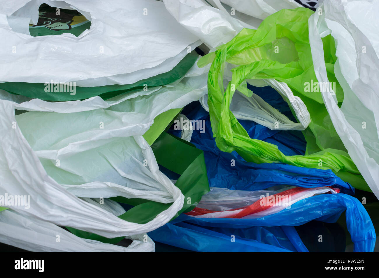 Multiple plastic shopping bags / carrier bags. Metaphor plastic bag tax, bag charge, war on plastic, plastic pollution UK. RM as identifiable colours. - Stock Image
