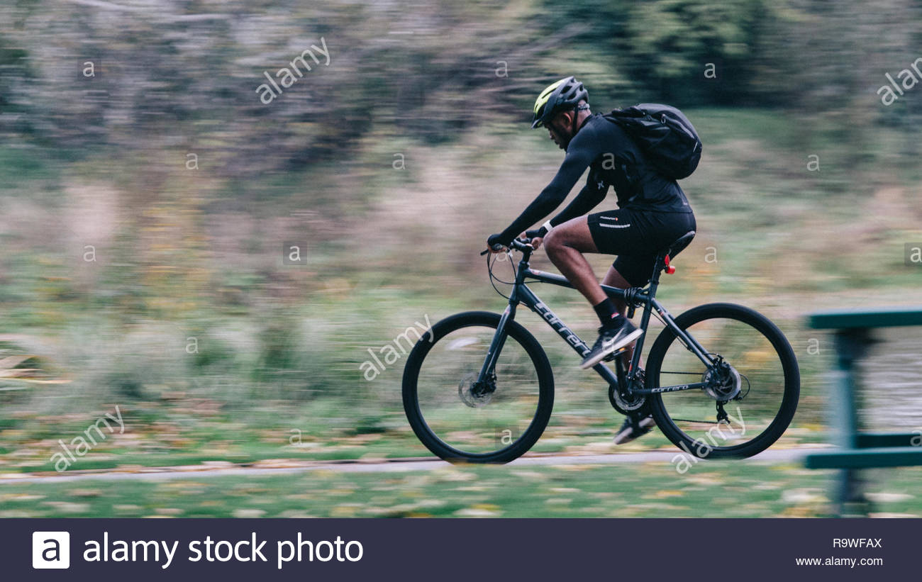A biker doing is morning exercise in a park of London. - Stock Image