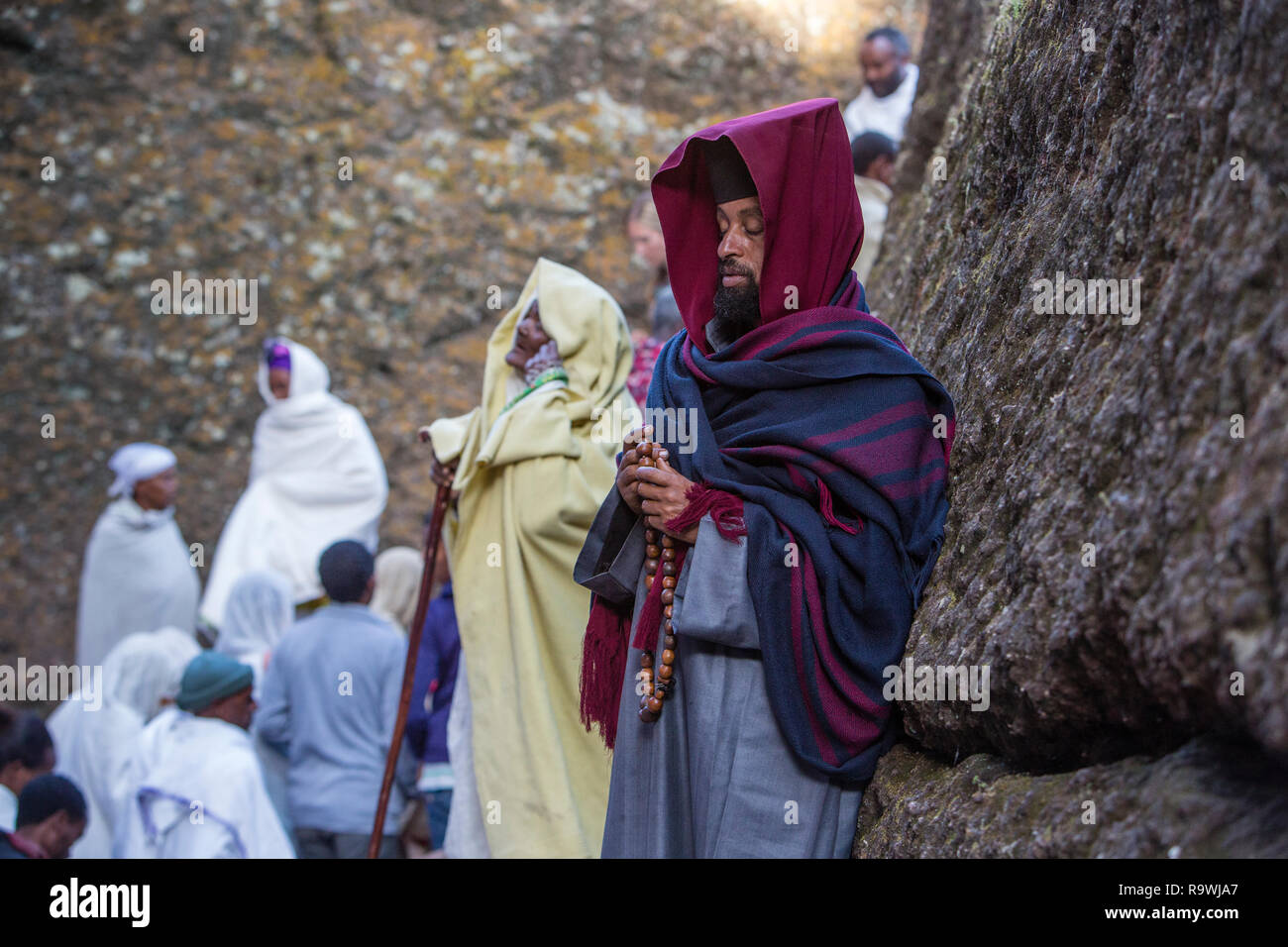Priests and worshipers during mass at the rock-cut church of House of the Saviour of the World at Lalibela, Ethiopia - Stock Image