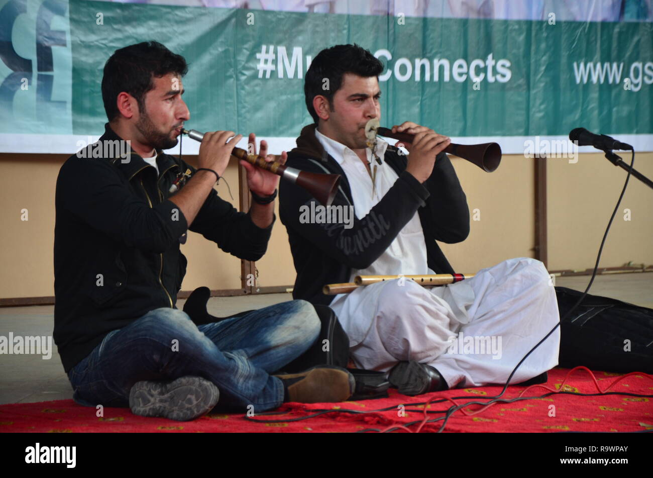 Two musicians play traditional flutes from gilgit baltistant region in north pakistan. - Stock Image