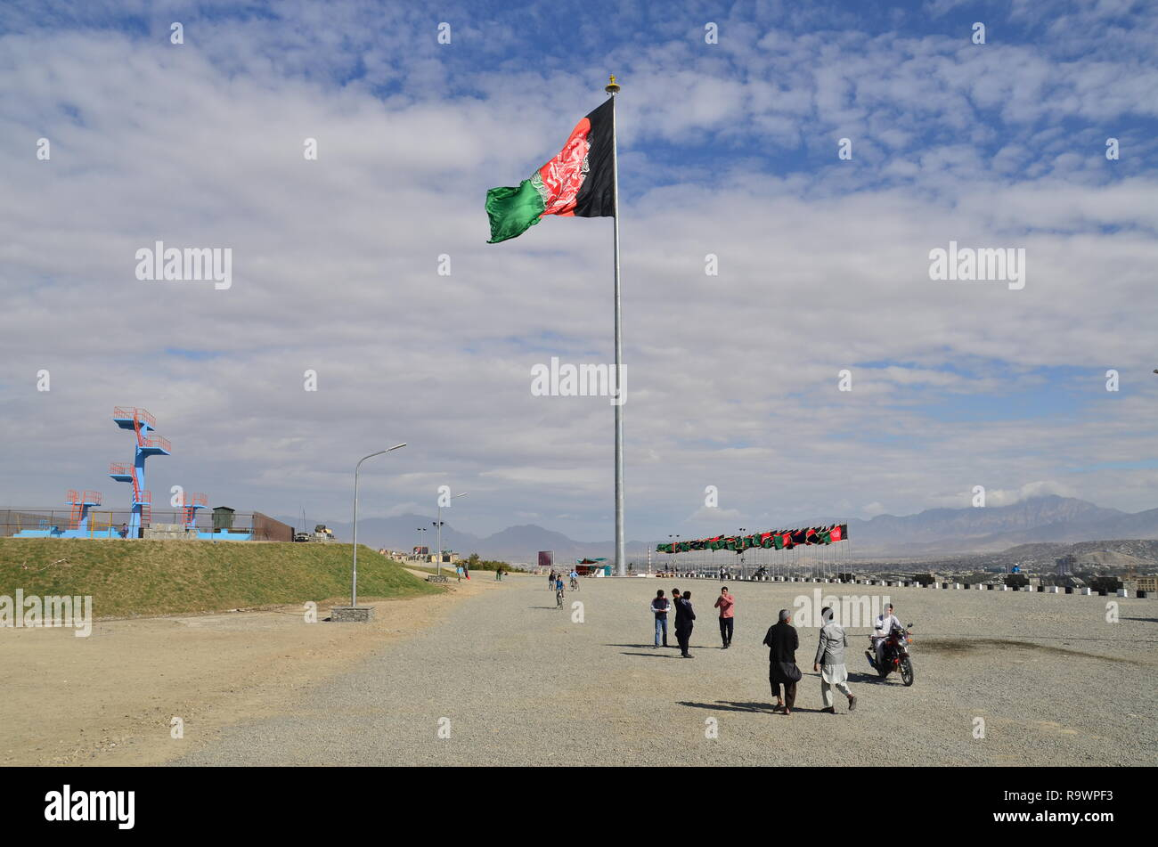 People walk by the flag of Afghanistan in a park in Kabul. - Stock Image