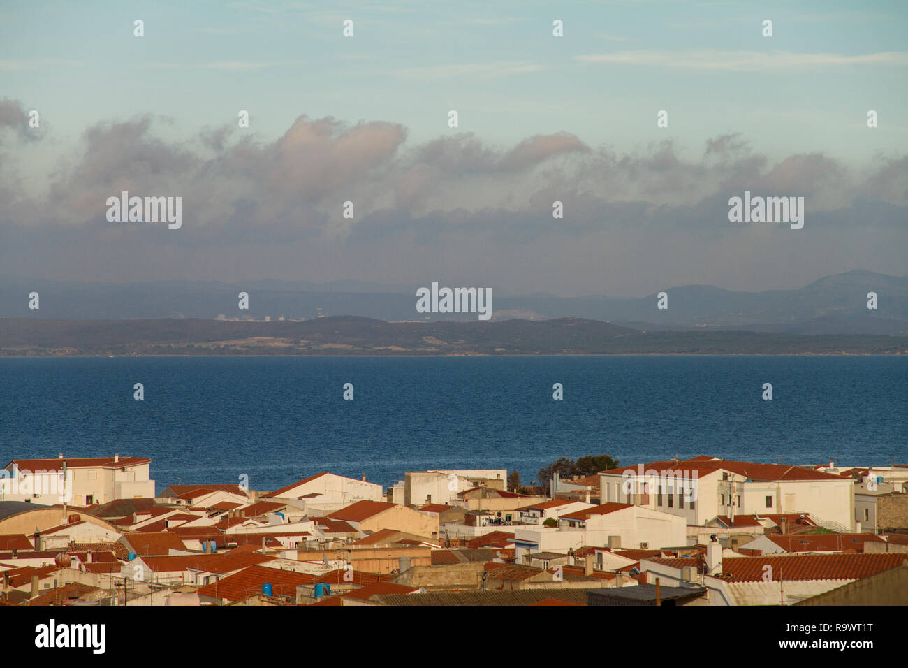 View of the roofs of a country in Sardinia with a varied sky in layers that generates a pleasant visual effect - Stock Image
