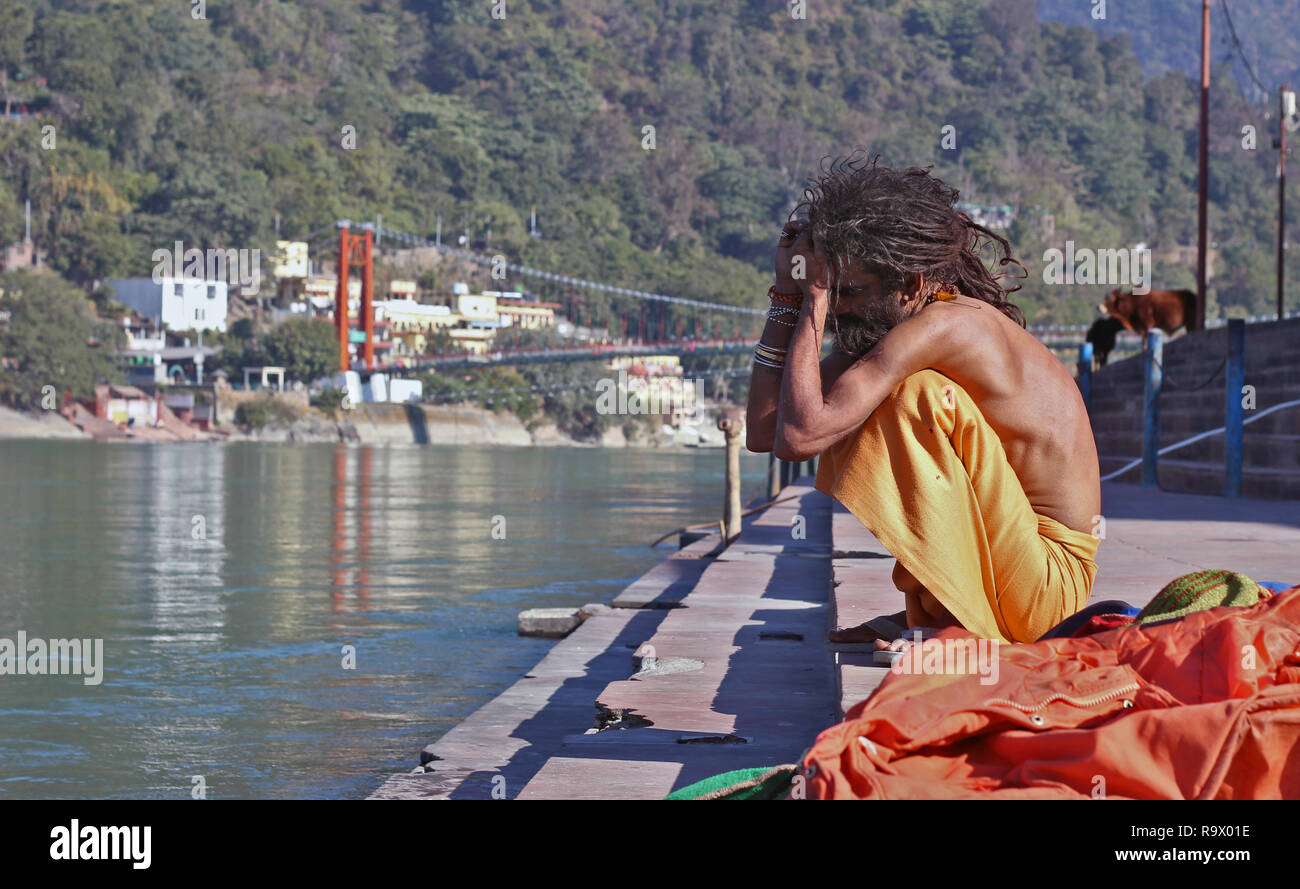 A Young Naga Sadhu with Skinny Body and Dreadlocked Hair sitting on the Bank of Holy River Ganges in Rishikesh, Uttarakhand, India - Stock Image