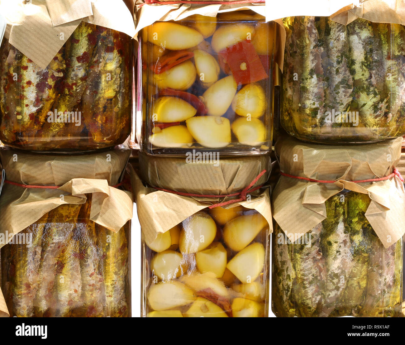 many jars with garlic cloves with peppers and marinated anchovies prepared by hand - Stock Image