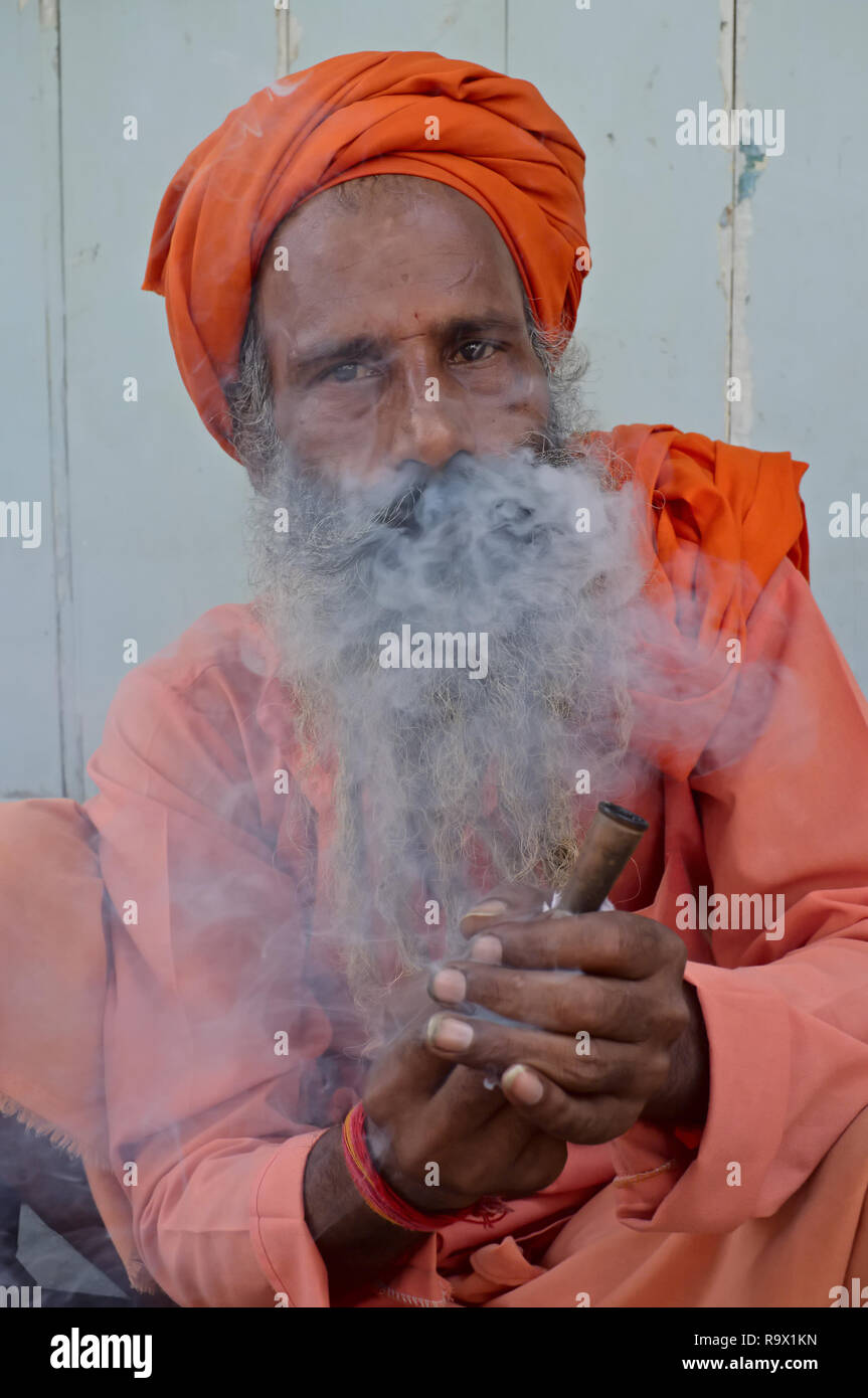 A sadhu or holy man in Mumbai, India, sqatting by the roadside smoking hashish, locally called charas, in imitation of his favority deity Shiva - Stock Image