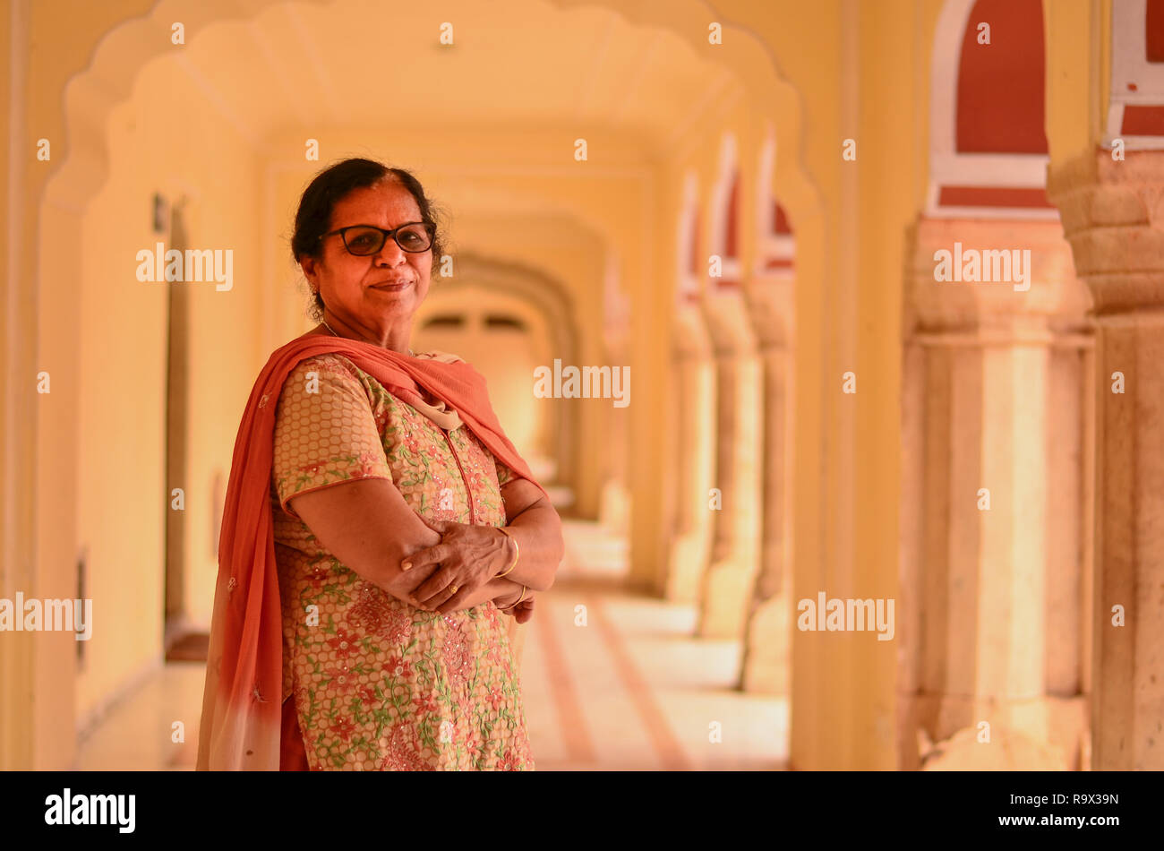 Happy looking senior Indian lady wearing traditional suit posing in the corridor of Jaipur's City Palace. - Stock Image