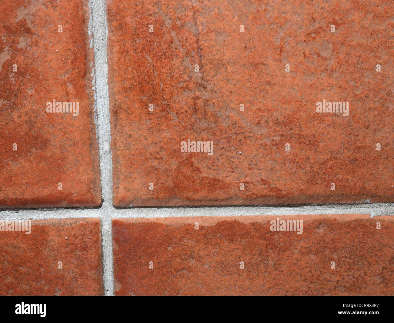 Horizontal rectangular tiled wall in bathroom in detail.  Tiles red and white chinks Stock Photo