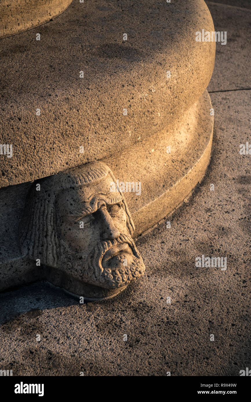 Stone Scandinavian head and face sculpture on outdoor seating, Stockholm, Sweden Stock Photo
