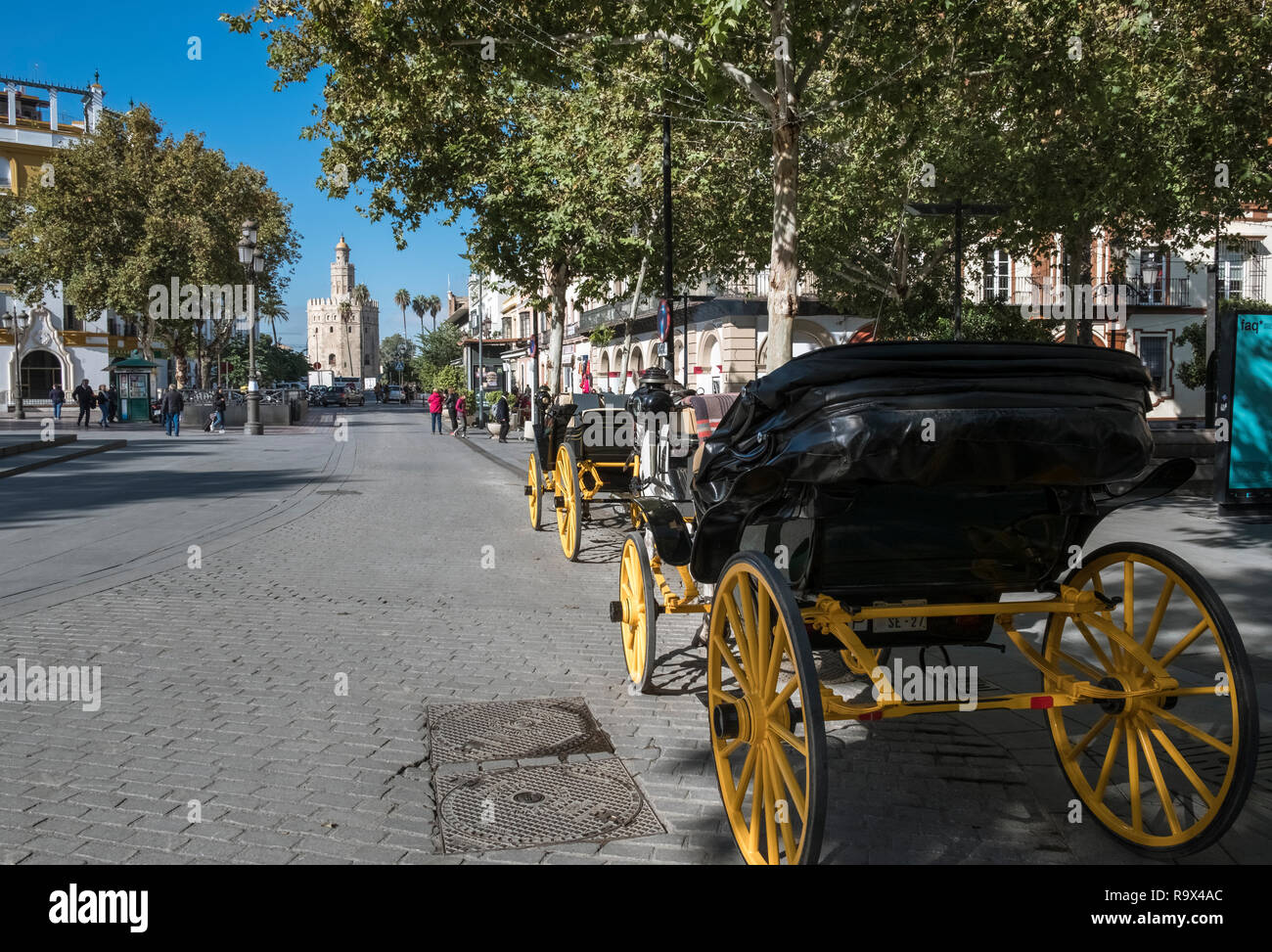 Horse drawn carriages waiting for customers, with historic defensive tower Torre Del Oro in the distance, Seville, Spain. Stock Photo