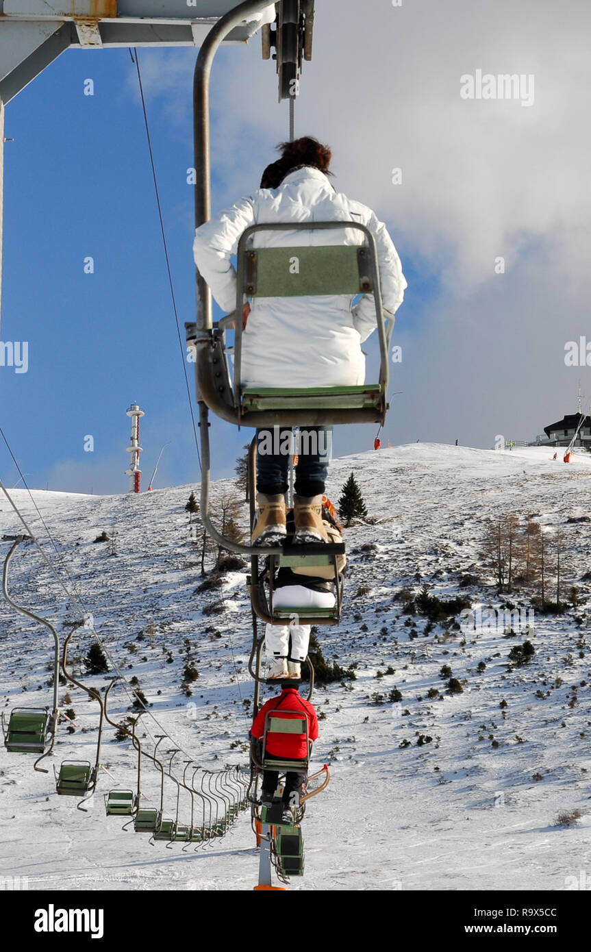 People, not recognizable, riding a skilift at Krvavec Alpine Mountain Ski Resort in Slovenia, vertical ortientation Stock Photo
