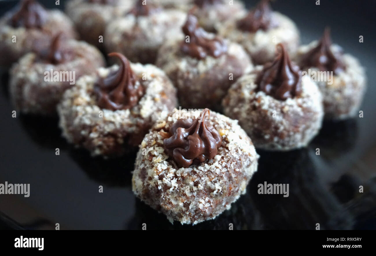 Chocolate delicious homemade praline decorated with grated hazelnut on the black plate Stock Photo