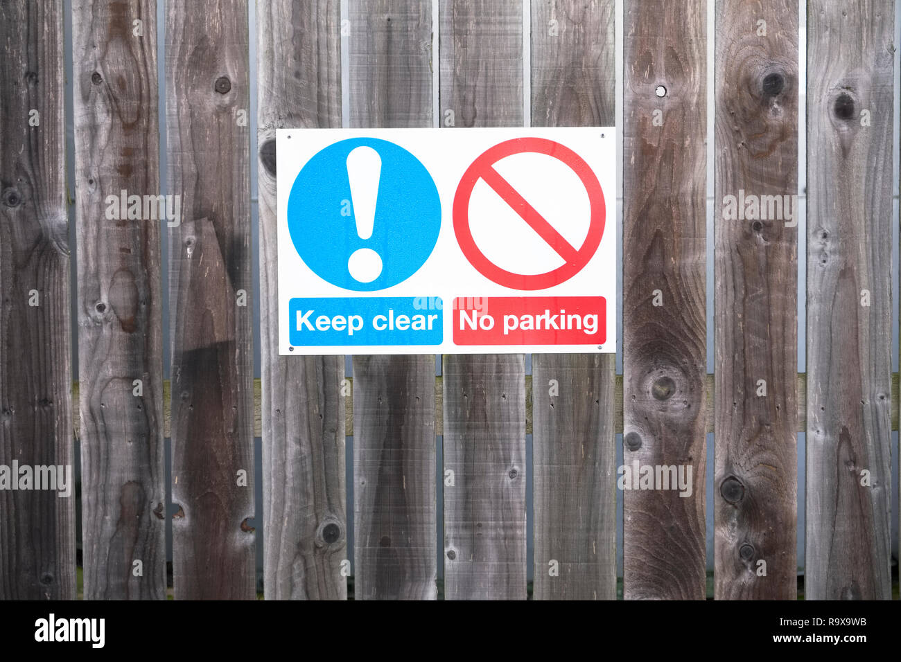 Keep clear no parking sign on wooden fence Stock Photo