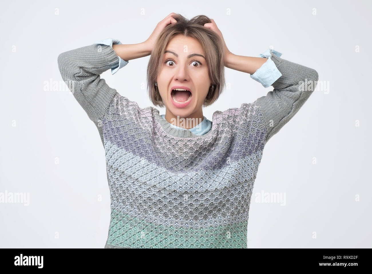 Shocked amazed young woman with hands on head standing and shouting - Stock Image