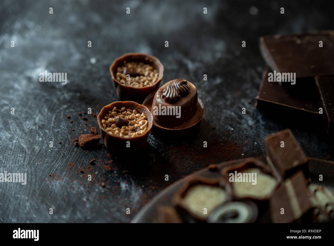 different, sweet pralines of dark, milk and white chocolate on a dark, wooden background Stock Photo