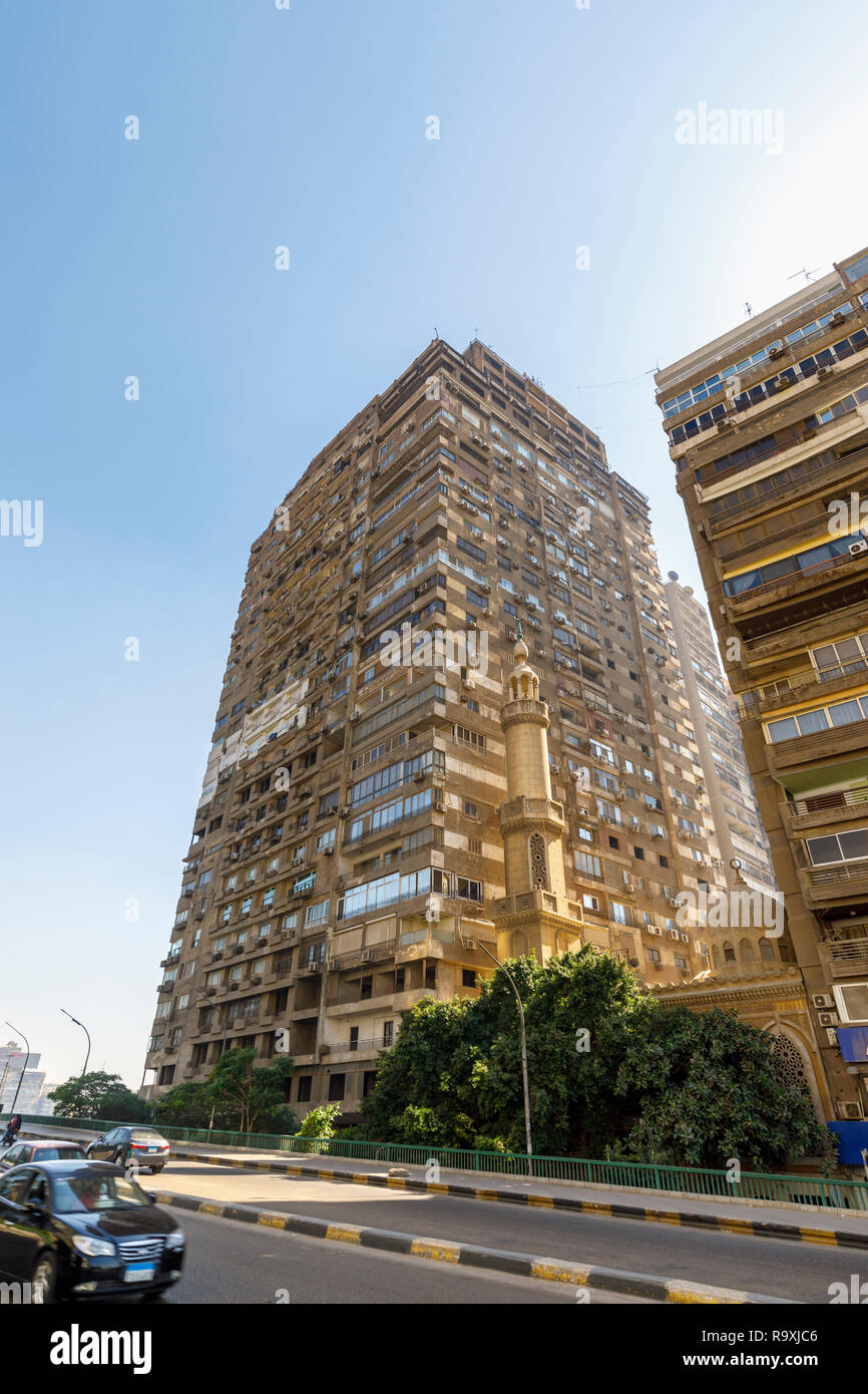 Street scene in Giza, Cairo, Egypt, typical large roadside residential apartment block with external air-conditioning units and a small mosque minaret Stock Photo