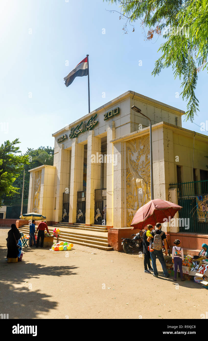 Entrance to Giza Zoo (Cairo Zoo), Giza, Cairo, Egypt, a popular local tourist attraction, with the Egyptian flag flying on a sunny day with blue sky - Stock Image