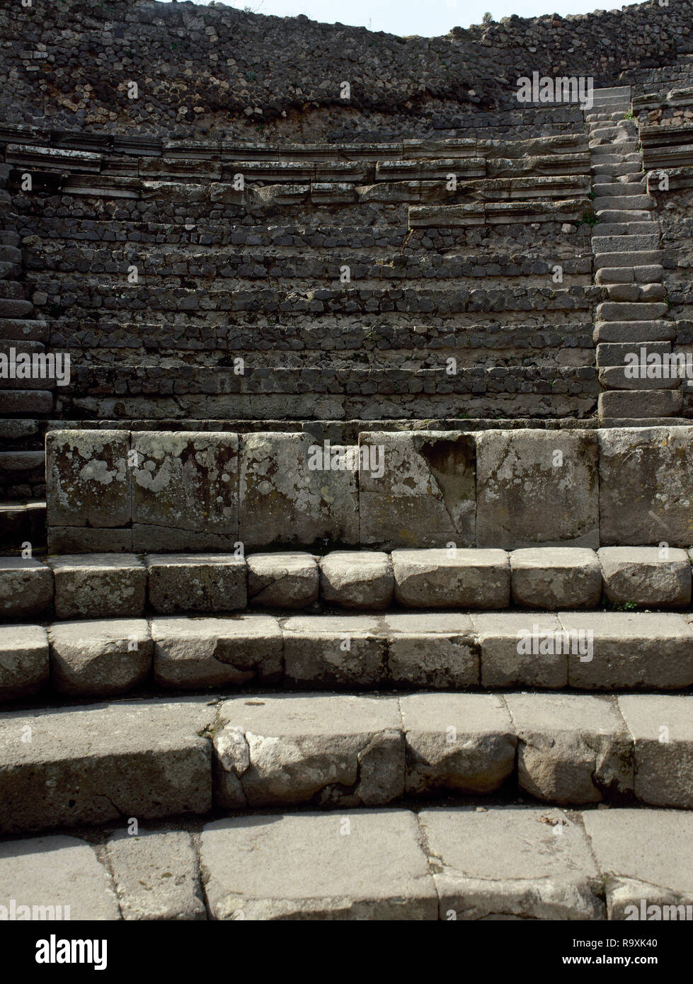 Italy. Pompeii. Ancient Roman city destroyed by the eruption of the Vesuvius in 79 AD. Small Theatre or odeon. Roofed theatre 'teatrum tectum' which sat 1500 spectators, built in 80 BC. View of  the 'cavea', the seating sections organised in three sections, corresponding to the social class of the spectators. The ima cavea, lowest part (for upper echelons of society), the media cavea (for men), the summa cavea, highest section (for women and children). Campania. - Stock Image