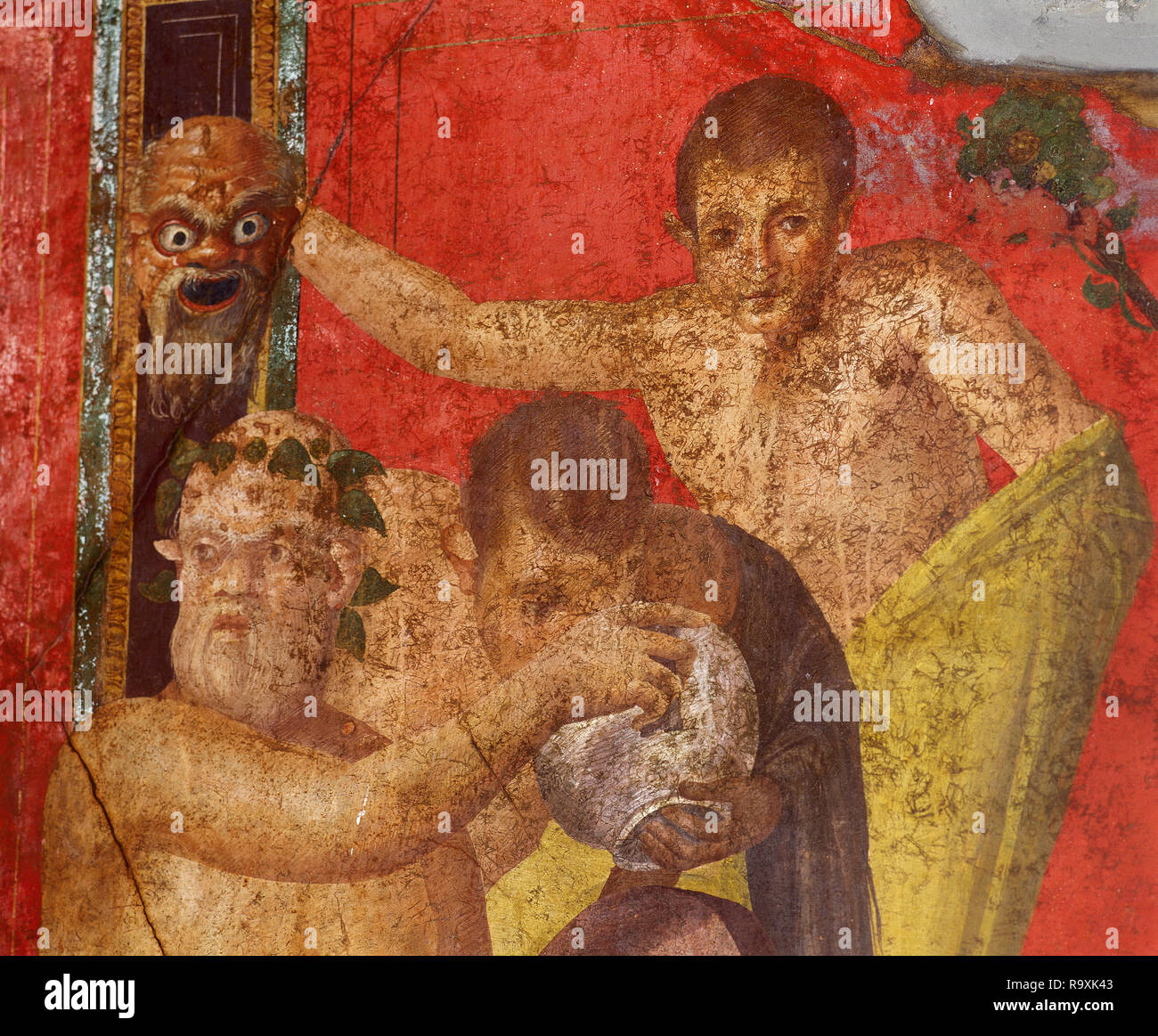 Italy. Pompeii. Villa of the Mysteries. Suburban Roman Villa. Dionysiac frieze, detail. Young satyr being offered a bowl of wine by Silenus while, behind him, another satyr holds up a frightening mask. Before 79 AD. Campania. - Stock Image