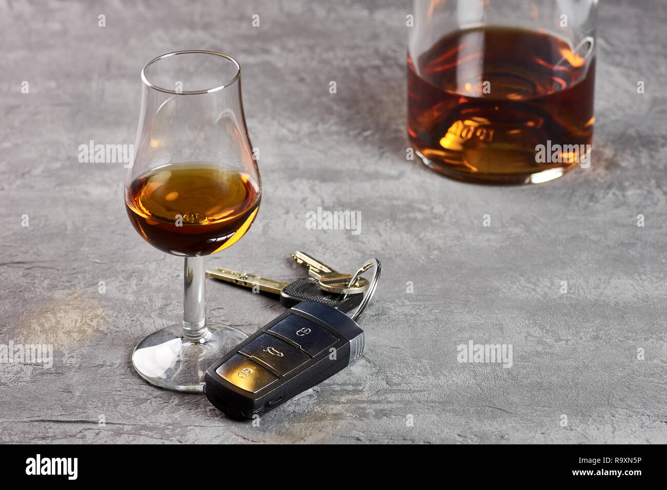 Glass and bottle of whiskey on a stone table top and car keys. Driving in drunkenness Stock Photo
